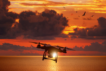 Silhouette of flying drone in glowing red sunset sky above sea