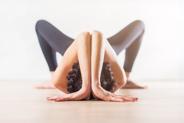 Woman doing yoga lying on floor in artistic aesthetical posture.
