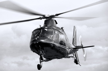 Black and white image of a helicopter hovering in flight