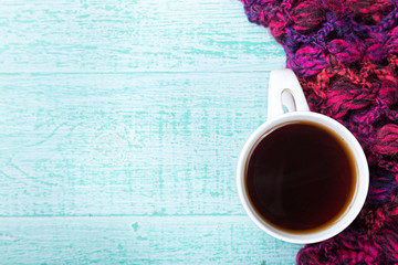 cup of hot black tea with steam in  knitted scarf