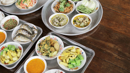 Set of Thai food Fried Mackerel with Shrimp Paste Sauce, Fried Egg with Climbing Wattle, Chicken Green Curry, Spicy minced pork, Noodles rice and curry, Stir-fried noodles, bamboo-shoot salad on tray