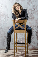 Young girl with curly hair in a black shirt, jeans and high boots cowboy western style