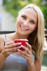 woman drinks coffe outdoor on a hot summer afternooon