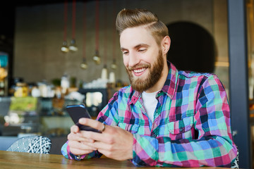 Happy hipster using his smartphone in cafe