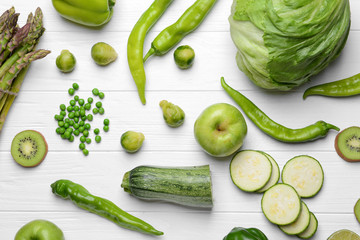 Green vegetables and fruits on wooden background