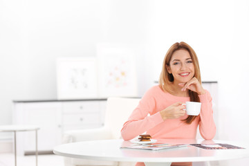 Young beautiful woman with cup of coffee sitting at table