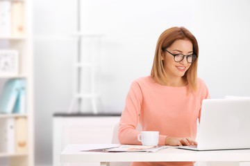 Young beautiful woman working on laptop with cup of coffee