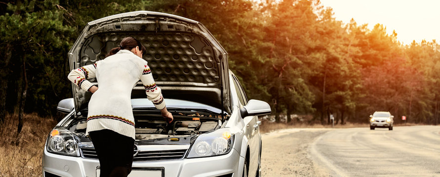young woman standing near the broken car. The girl opened the hood and look at the engine. Refit woman car