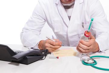 Doktor schreibt ein Rezept und hält Medizin in der Hand