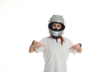Woman show by fingers on wearing white t shirt. Motorbiker girl in black and white helmet on neutral background. Copy space for goods or advertising motor text.