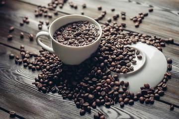 mug of coffee, coffee beans, saucer on the table