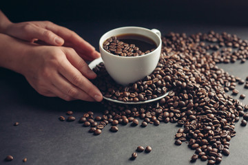 coffee beans, black background, cup, saucer, coffee beans in hand