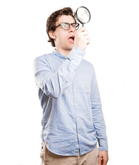 Surprised young man using a magnifying glass