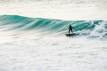 Surfer on green wave in ocean.