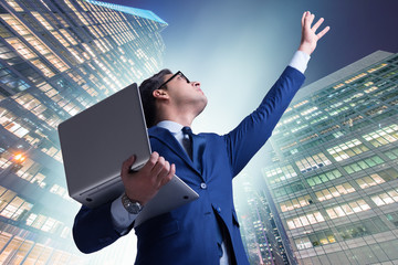 Businessman with laptop against the building