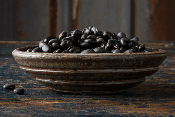 Dried black beans in a pottery bowl