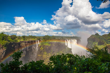 Wall Mural - Victoria Falls from the side.  A rainbow and blue sky with clouds on a sunny day