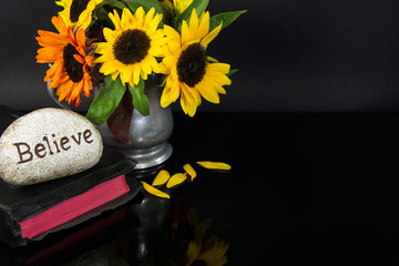 word believe carved in stone on Bible with sunflower bouquet in pewter pitcher