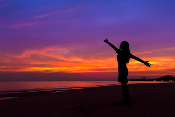 Silhouette of woman with hands up while standing on sea beach at