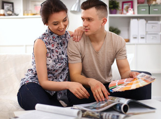 Happy young couple sitting together on the sofa