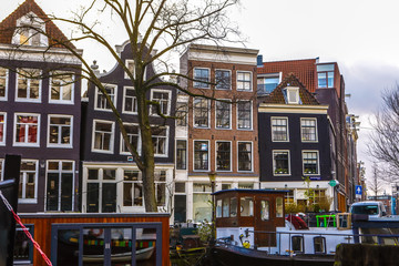 AMSTERDAM, NETHERLANDS - JANUARY 10, 2017: Famous vintage buildings of Amsterdam city at sun set. General landscape view at tradition Dutch arcitecture. January 10, 2017 - Amsterdam - Netherlands..