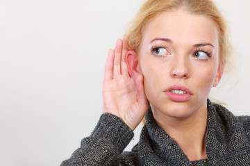 Woman put hand to ear for better hearing