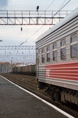 The last car on the Trains-Siberian Railway on the track in Russia. A neighboring track has a freight train with colorful cars. Power lines are above.