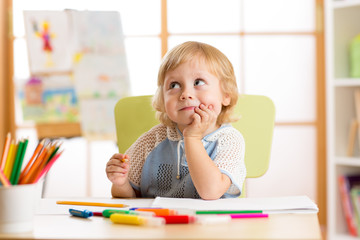 Smiling child having an idea while drawing in nursery room