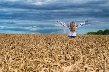 Girl rise up among the wheat field