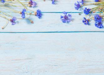 cornflowers over blue wooden background