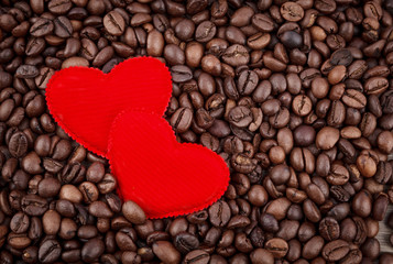 Red two hearts and coffee beans on wooden background