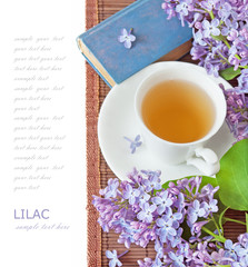 lilac flowers with cup of tea nad book. Teacher's day concept