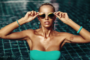 Vogue style fashion portrait of beautiful chic woman in water