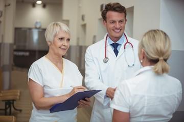 Doctor shaking hand with nurse in corridor