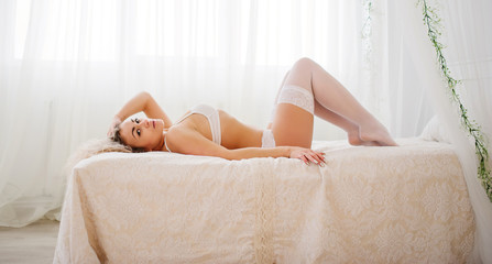 Curly blonde girl in underwear lying in bed indoor.