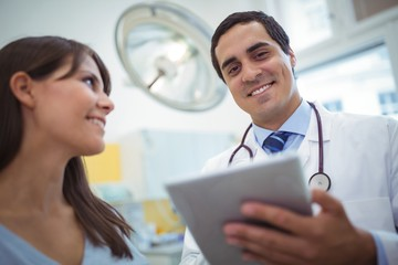 Portrait of doctor using digital tablet while consulting patient