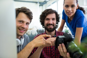 Team of graphic designers holding camera