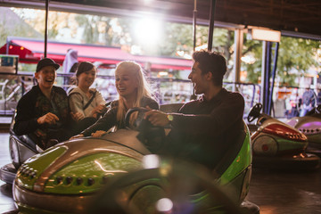 Friends having fun on bumper cars in amusement park
