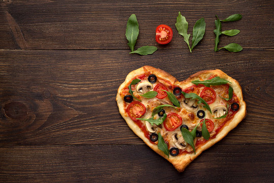Heart shaped pizza for Valentines day on dark rustic wooden background with text love.