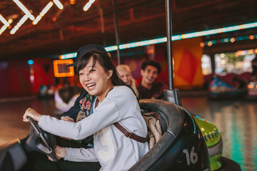 Happy young girl driving a bumper car