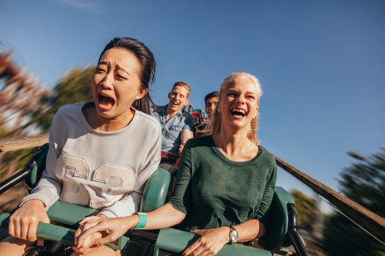 Friends cheering and riding roller coaster at amusement park