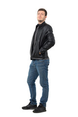 Side view of young casual man in jeans and leather jacket smirking at camera. Full body length portrait isolated over white background.
