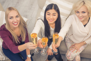 Toned top view picture of best friends girls drinking champagne while spending free time having party at home. Beautiful women smiling for camera.