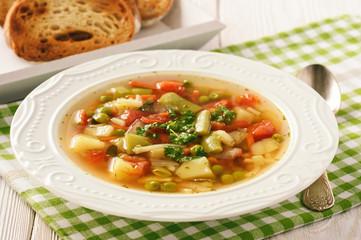 Vegetarian vegetable soup on wooden bakcground.