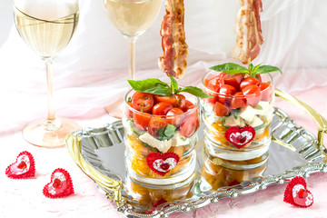 Festive caprese salad with fried bacon on skewers in glasses