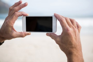 Close-up of mans hand taking picture on mobile phone on beach
