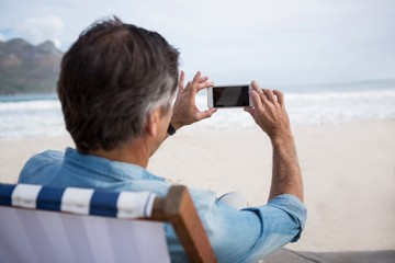 Rear view of man taking picture on mobile phone at beach