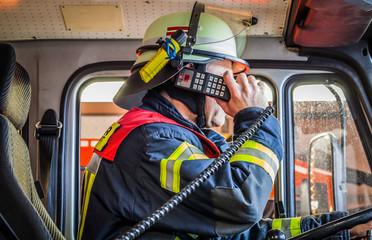 HDR - Feuerwehrmann im Einsatzfahrzeug im Einsatz mit Funkgerät
