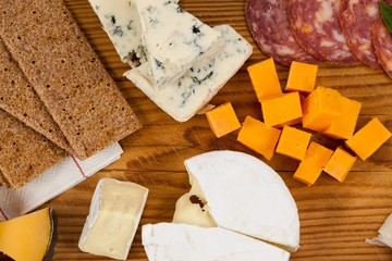 Variety of cheese with biscuits on chopping board