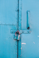 Hanging metal lock on emerald paint color metallic door. Closed private object vintage style
